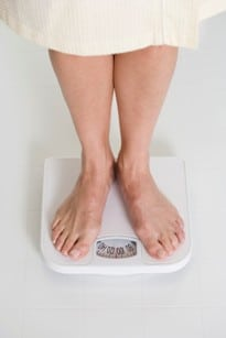 A person weighing themself as part of our medical weight loss treatment in Marietta, GA